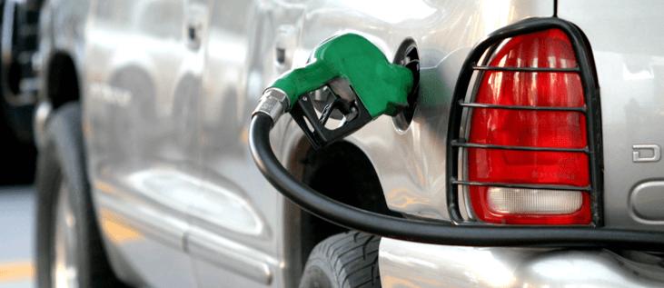 Un carro en una gasolinera con una manguera de combustible