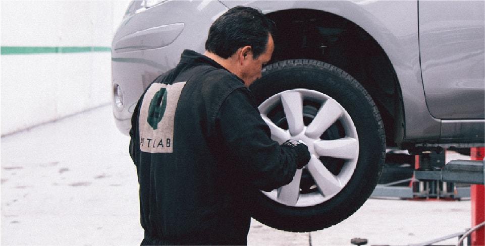 Hombre en un taller mecánico comprobando el balanceo de un carro