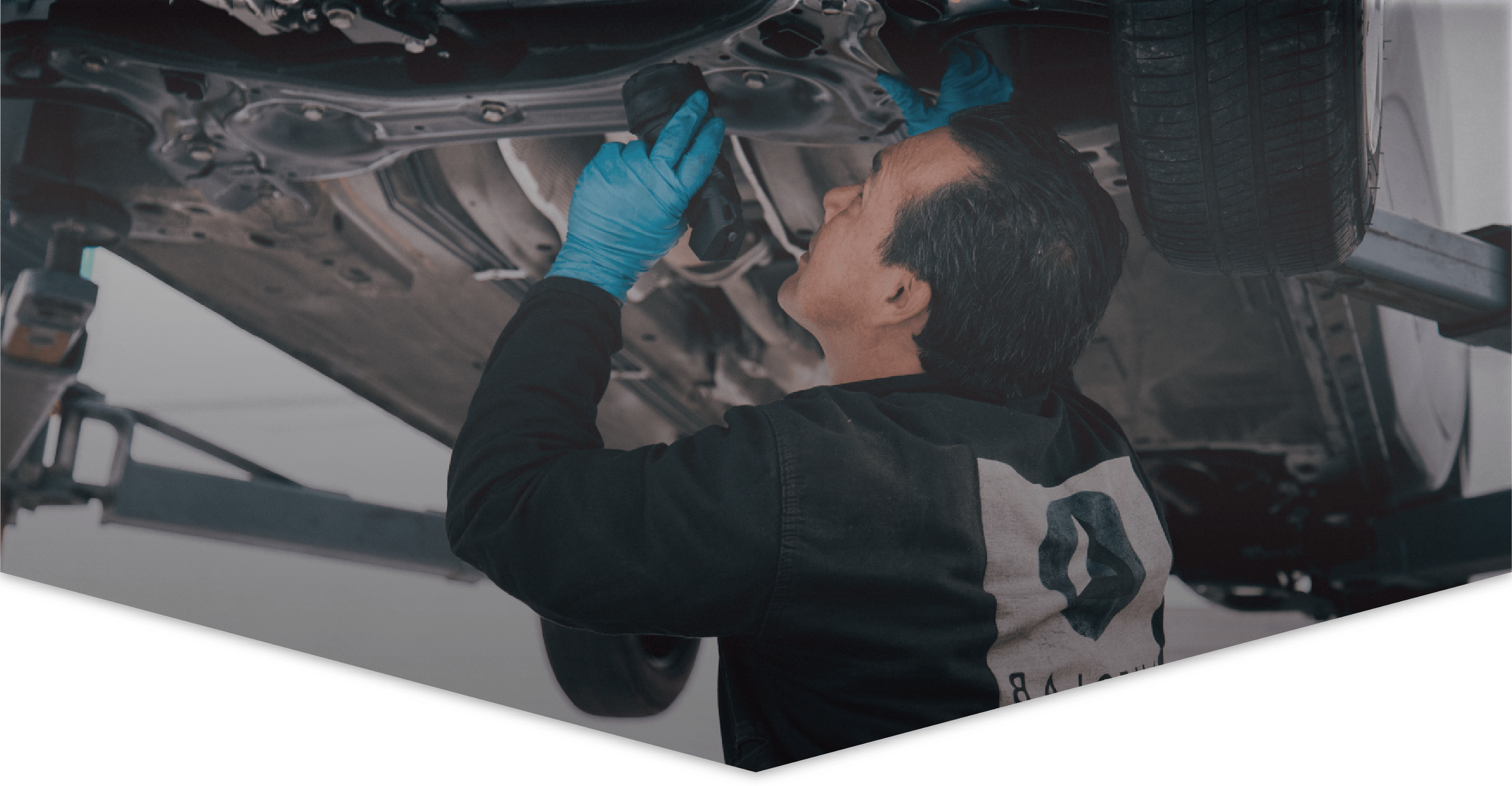 Mecánico de Autolab inspecciona un carro desde abajo hacer un mecánico básica