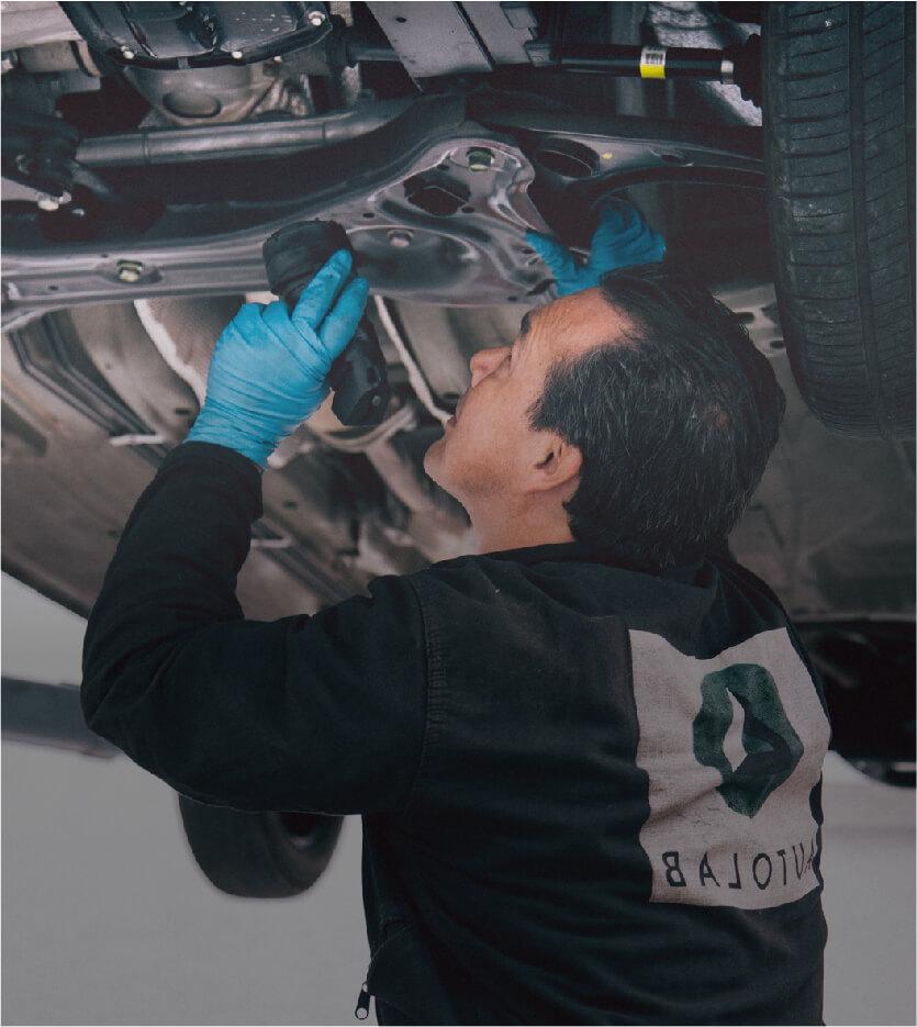 Mecánico de Autolab inspecciona un carro desde abajo